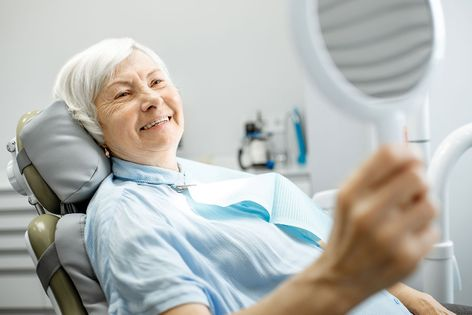 smiling old lady looking at a mirror